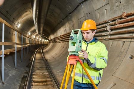 teodolito: Topógrafo con el nivel teodolito en las obras de construcción del túnel de metro