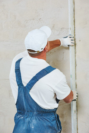 Plasterer at indoor wall renovation