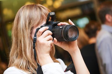 reportero: Fotógrafo mujer en el trabajo en el interior