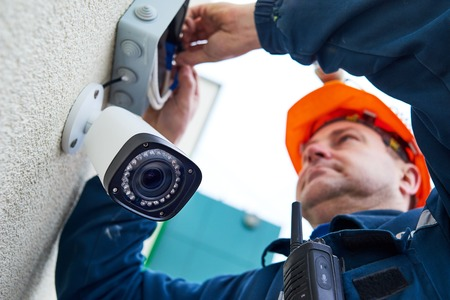 Technician worker installing video surveillance camera on wall