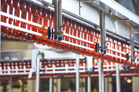 intoxicating: Plastic bottles for beer or carbonated beverage moving on conveyor