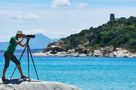 photo: Photographer with tripod shooting sea landscape