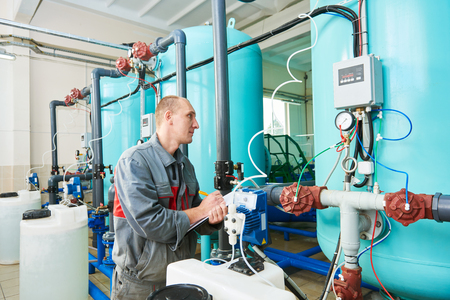 filters: serviceman operating industrial water purification or filtration equipment Stock Photo