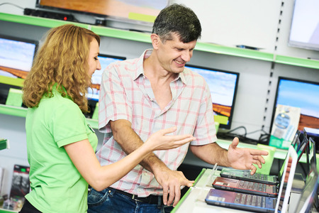 purchaser: Seller assistant woman help purchaser choosing laptop computer
