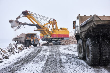 excavator loading granite or ore into dump truck at opencast