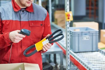 Lavoratore del magazzino che esegue la scansione del pezzo di ricambio dell'automobile con lo scanner del codice a barre del laser