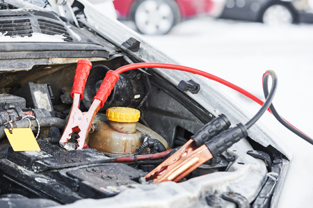 boosting: Charging automobile discharged battery by booster jumper cables at winter Stock Photo