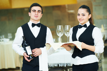 service: young waiter and waitress at service in restaurant Stock Photo