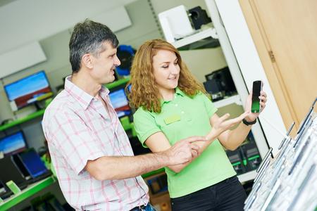 supermarket: Seller assistant woman help purchaser choosing mobile phone