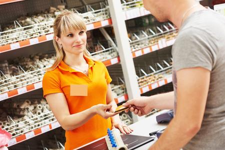 Kasse Arbeiterin Zahlungskarte an Hardware-Shop akzeptieren