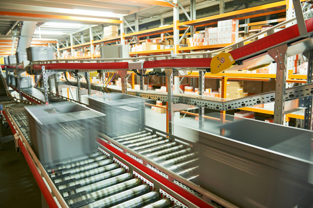 storage: Automated warehouse. Boxes with spare parts moving on conveyer Stock Photo