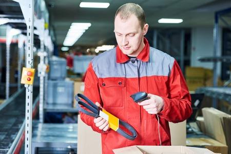 werknemer man aan het werk met laser barcodescanner op auto reserveonderdelen magazijn Stockfoto
