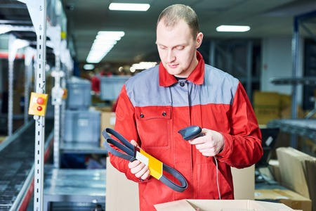 worker man working with laser barcode scanner at automobile spare part warehouse