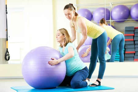 healthy body: pregnant woman doing fitness ball exercise with trainer
