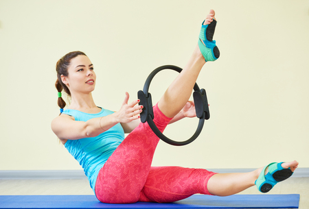 Fitness yoga. Woman doing stomach pilates exercises in gym