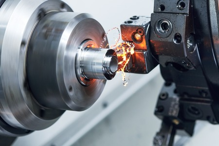 alloy: metalworking industry. cutting tool processing steel metal detail on turning lathe machine in workshop