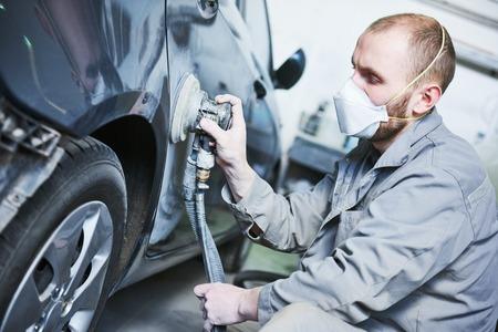 rennovation: auto repairman grinding automobile car body
