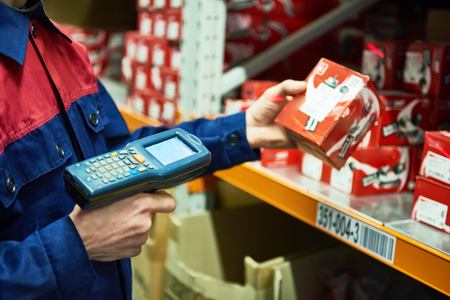 Lavoratore del magazzino che esegue la scansione del pezzo di ricambio dell'automobile con lo scanner del codice a barre del laser Archivio Fotografico - 77052087