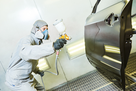 painting: car repairman painter in chamber painting automobile door