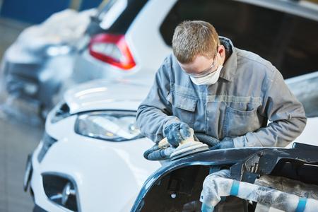 rennovation: auto repairman grinding autobody bonnet Stock Photo