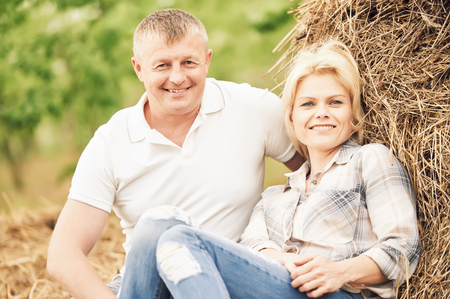 smiling adult couple near haystack at countryside