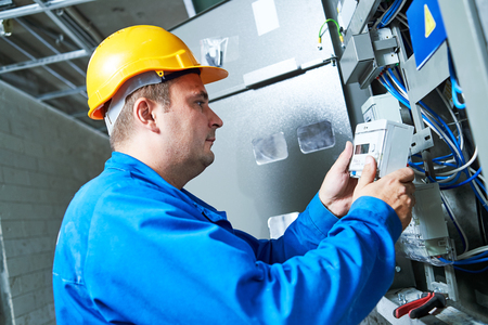 industry: Electrician installing energy saving meter
