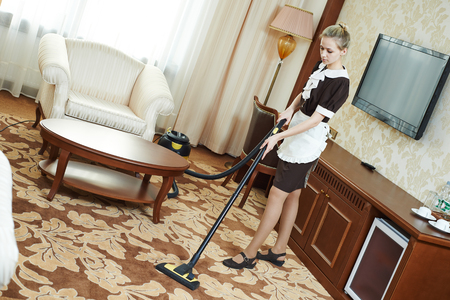 carpet clean: Hotel service. female housekeeping worker with vacuum cleaner Stock Photo