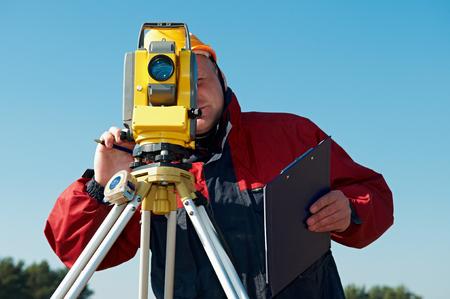 topografo: Topógrafo trabajador con teodolito