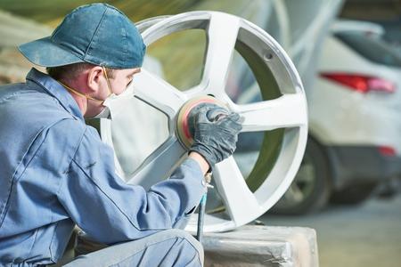 industry: repair mechanic worker with light alloy car wheel disk rim