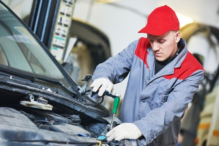 Auto repair service. Mechanic works with spanner