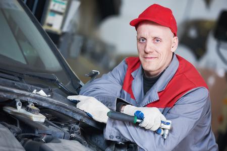 Service de réparation automobile. Portrait de travailleur mécanique avec clé