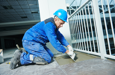 tiler at industrial floor tiling construction or renovation Stock Photo
