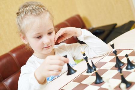 Child girl playing chess game