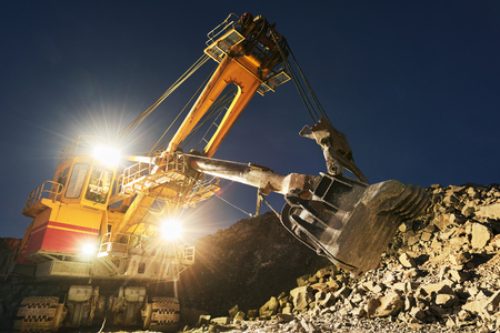 Mining construction industry. Excavator digging granite or ore in quarry
