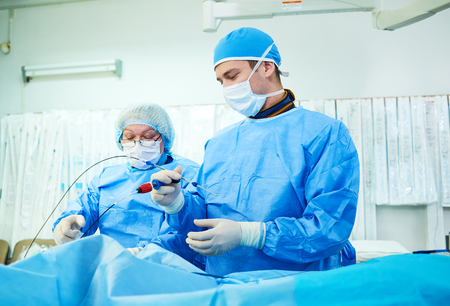 Interventional cardiology. Male surgeon doctor at operation Imagens