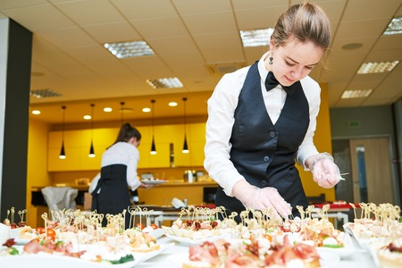 hotel staff: Restaurant waitress serving table with food Stock Photo
