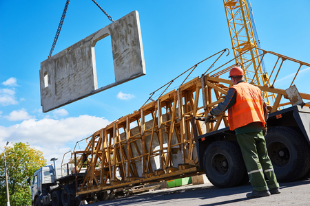 warehouse building: Construction industrial worker operating hoisting process of concrete slab Stock Photo