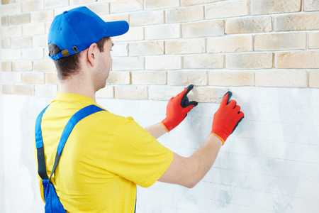 wall facing work with brick by professional bricklayer worker photo