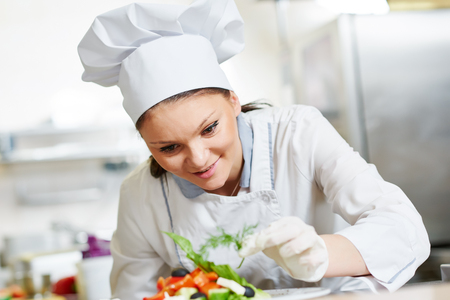 hotel staff: female cook chef decorating prepared salad food Stock Photo
