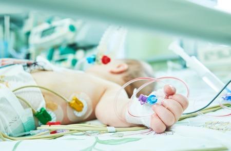 Newborn child inside incubator in hospital