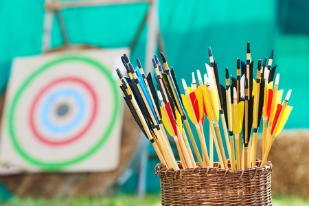 Archery concept. Basket with arrows for bow in front of target during competition