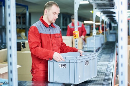 dispatcher: worker man with box near conveyer at automobile spare part warehouse