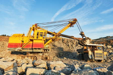 Heavy excavator loading granite rock or iron ore into the huge dump truck at opencast mining quarry