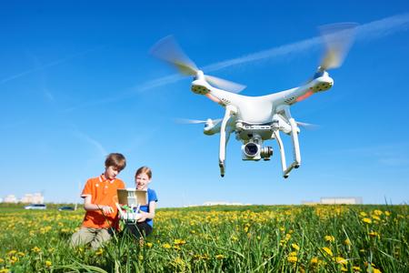 Kinder, die mit fliegender Drohne bei Sonnenuntergang arbeiten Standard-Bild - 83804421