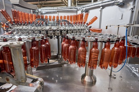 Plastic bottles for beer or carbonated beverage moving on conveyor