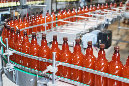 technology: Plastic bottles with beer or carbonated beverage moving on conveyor