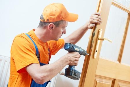 Timmerman bij de deurslot installatie of reparatie Stockfoto