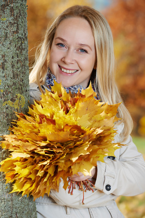 Woman with maple leaves at autumn photo