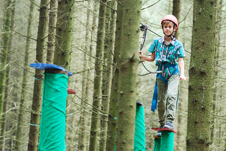 boy at climbing activity in high wire forest park Stock Photo