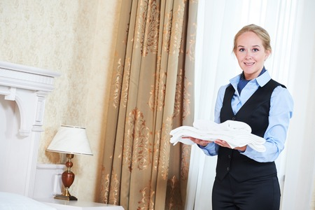 Hotel female housekeeping worker charmbermaid with linen Stock Photo